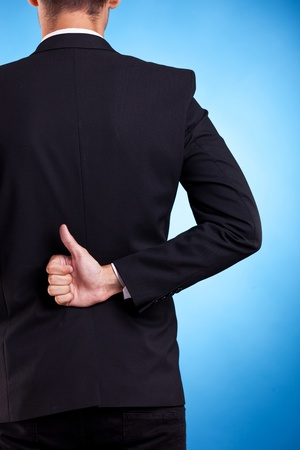 Business man hand with thumbs up ok sign at his back, on blue background photo