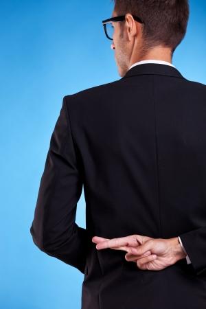 mani incrociate: uomo d'affari con le dita incrociate dietro la schiena isolato su sfondo bianco Archivio Fotografico