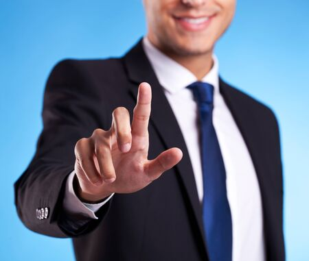 Business man pressing an imaginary button on blue background photo