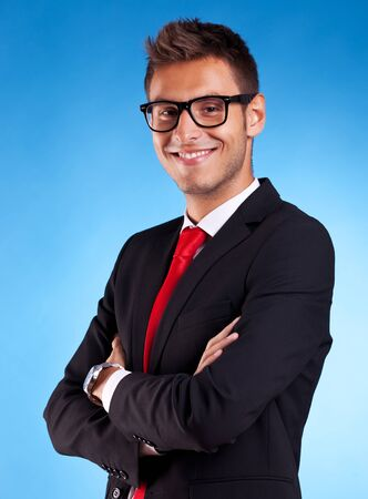 young business man smiling with his arms crossed  on blue background photo