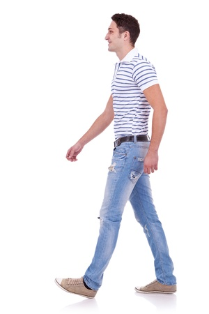 see side: side view of a fashion man walking forward over white . young casual man walking from right to the left of the camera
