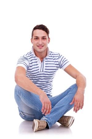 hombre sentado: joven hombre feliz ocasional sentado en el estudio, aislado