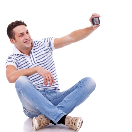 young casual man taking a picture of him self using a smart phone photo