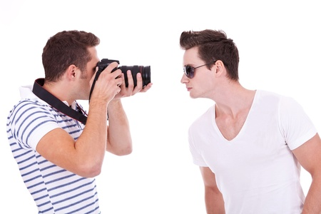 young photographer during a photo shoot with a male model, on white background photo