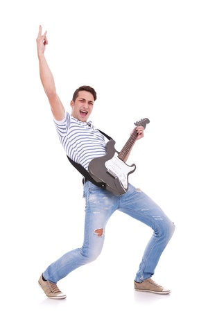 young casual man playing an electric guitar and making a rock and roll hand gesture while screaming photo