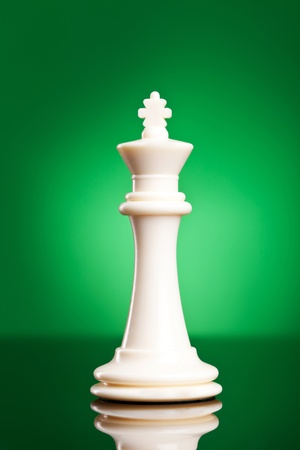 Photo of a single chess piece - a white king. The chess pieceon green background  photo