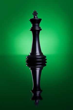 Piece of chess. The black king standing on a green background with a reflection   photo