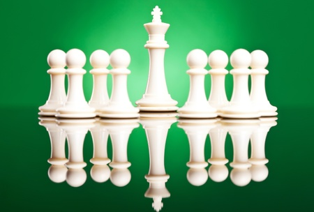 white pawns protecting their leader, the white king - chess pieces on green background photo