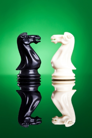 two piece: Chess knights on green background with reflection on the floor - white and black knights face to face Stock Photo