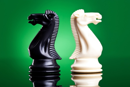 chess knight: back to back knights on a green background with reflection - chess pieces