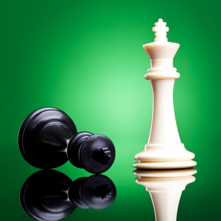 defeated: Black and white chess kings , the defeated white king is down - chess pieces
