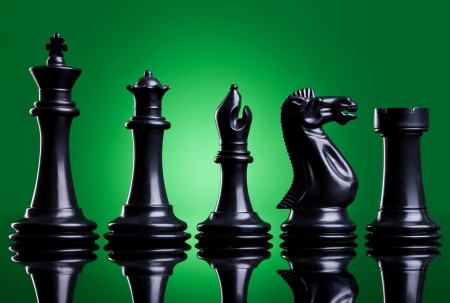 bishop chess piece: Black chess pieces in order of decreasing importance, on green background Stock Photo