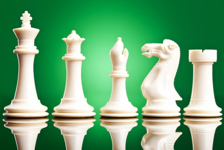 white chess pieces in order of decreasing importance, on green background Stock Photo - 14107280