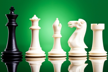 black king near white chess pieces on green background photo