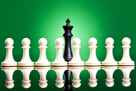 white pawns in front of a black king - chess pieces on green background photo