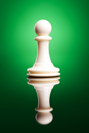 Chess figure - white pawn - on a green background   photo