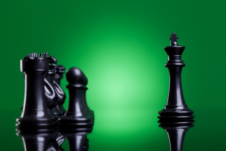 chessmen: black king leading his army - side view of a black king standing in front of the rest of the chess pieces on green background