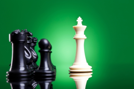 leading light: white king in front of the black chess pieces - on green background Stock Photo