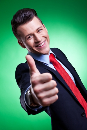 Happy business man on green background holding thumbs up ok sign Stock Photo - 14637755