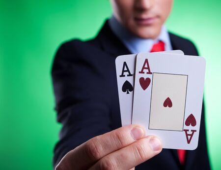 close up picture of a young business man holding a pair of aces on green background Stock Photo - 14637738