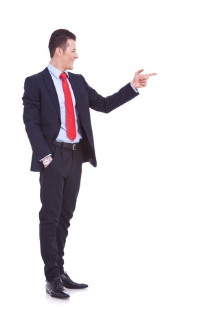 full body picture of a handsome young business man pointing to his side on white background