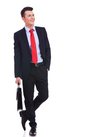 young business man with suitcase standing with his hand in pocket and looking to a side on white background Stock Photo - 14637620