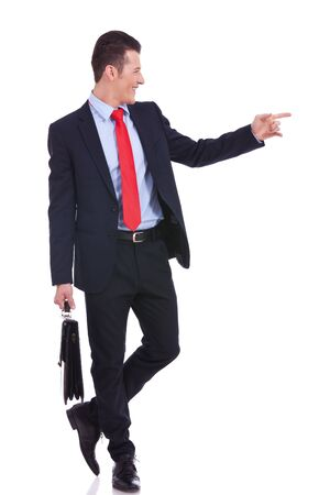 full suit: Handsome young business man happy smile pointing finger to empty copy space, while holding a briefcase Stock Photo