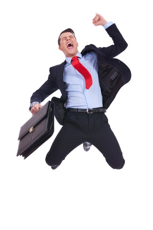 rooting: super excited business man with briefcase jumping in mid air cheering and celebrating his success  Stock Photo