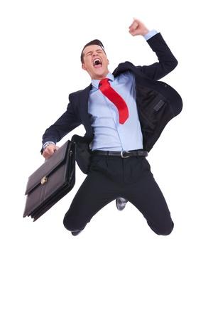 may�sculas: super hombre de negocios emocionado con malet�n de salto en el aire que anima y que celebra su �xito