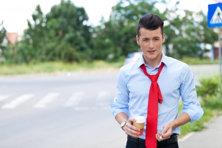 young business man having a break , drinking coffee and smoking a cigarette photo