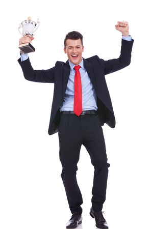 holding aloft: full body picture of a business man holding a gold trophy, isolated