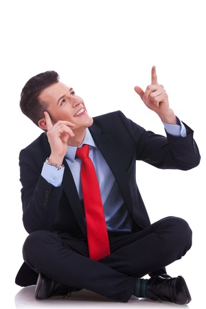 sitting on floor: young seated business man looking up above his head and pointing to empy copy space Stock Photo