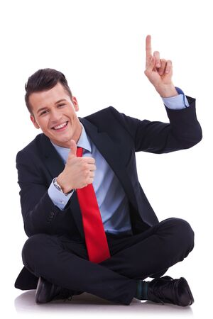 seated young business pointing and showing you something above his head and gibing the ok for it Stock Photo - 14637705