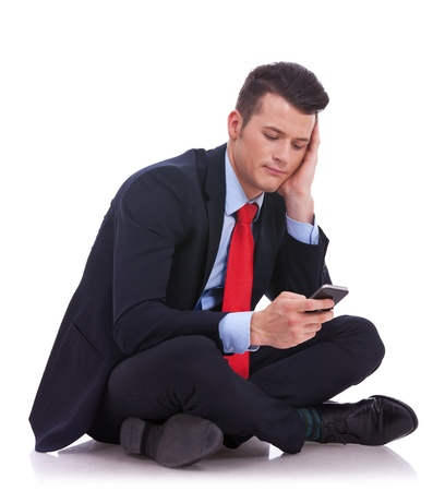 pensive young business man is reading a text message while sitting on a white background photo