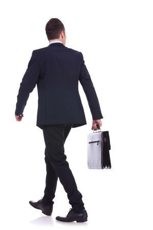 estuche: Vista posterior de un hombre de negocios caminando con un maletín y mirando a su lado en el fondo blanco Foto de archivo