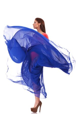 flying woman: side view of a beautiful woman in blue waving flying dress on white background