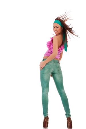 back view of a sexy young woman in jeans and high heels shoes looking to to the camera on white background photo