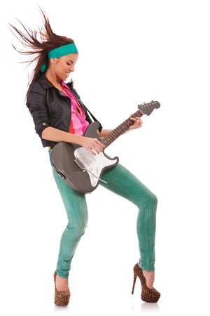 side view of a passionate woman guitarist playing rock and roll on an electric guitar photo