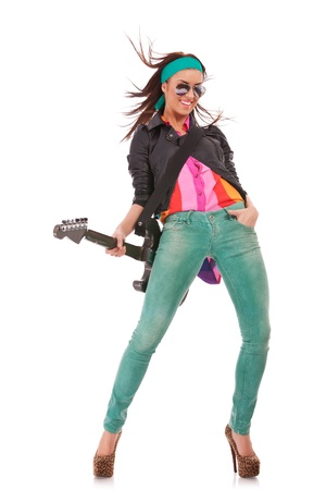 young sexy woman posing for the camera on white background, holding an electric guitar at her back, waiting for some rock and roll