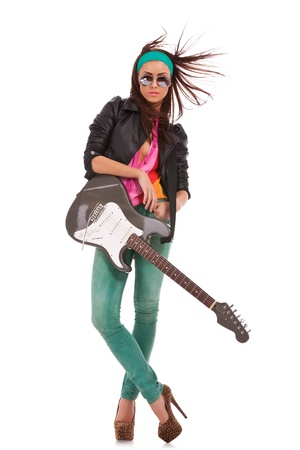 glam rock: relaxed rock and roll babe with windy hair, leaning against her electric guitar on white background