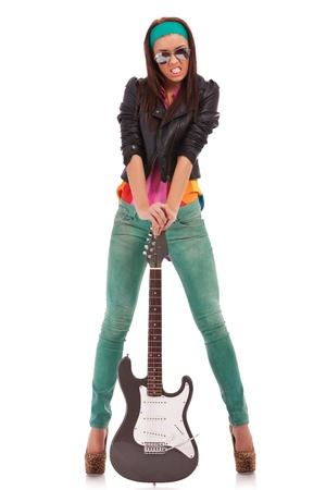 hot rock and roll woman wearing high heels shoes and sunglasses screaming while holding her electric guitar on the ground, on white background Stock Photo - 14637677
