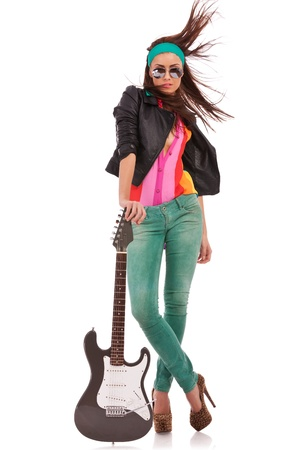 rock n roll: hot rock and roll woman wearing high heels shoes, with windy har, holding her electric guitar on the ground, on white background Stock Photo