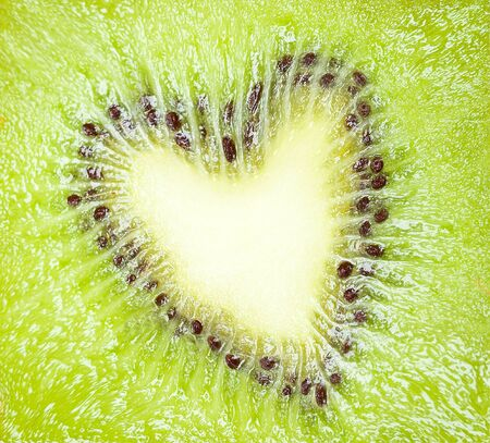 Texture section kiwi fruit in shape of a heart - love for the fruits concept photo