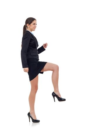 isoladed: Young attractive business woman stepping on imaginary step. Isoladed on white.