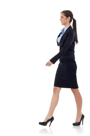 business people walking: young business woman  walking. She is smiling and looking away from the camera isolated over white background