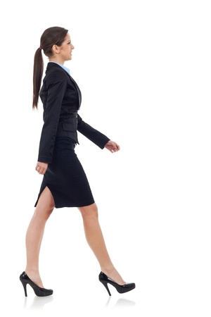 walking: young business woman walking. She is smiling and looking away from the camera isolated over white background