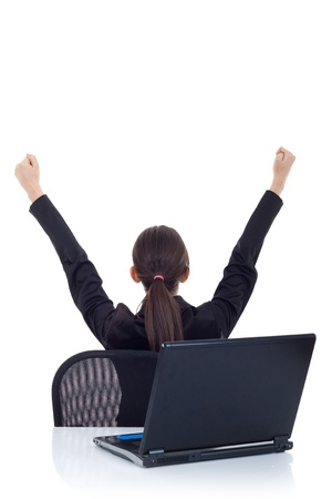 portrait of a young business woman from behind, cheering. Back view of a victorious young business woman in front of laptop. Isolated on white  photo
