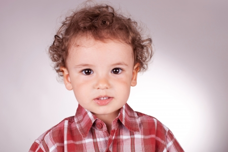 mouth opened: portrait of a lovely little boy looking in the camera with his mouth opened. on gray background Stock Photo