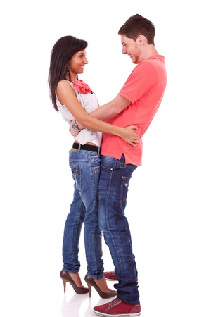 eachother: Side view of a young couple holding eachother by the waist , face to face, and smiling