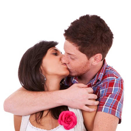 A portrait of a young couple kissing, over white background photo